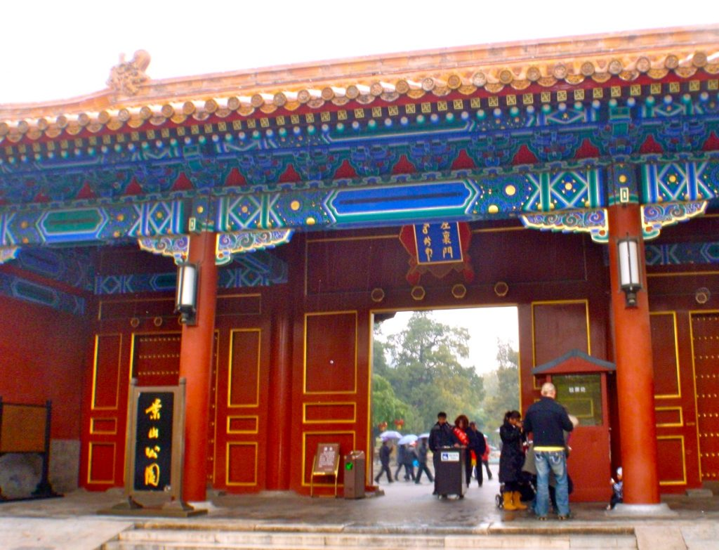 En stor röd dörr öppnas in till Jingshanparken i Peking