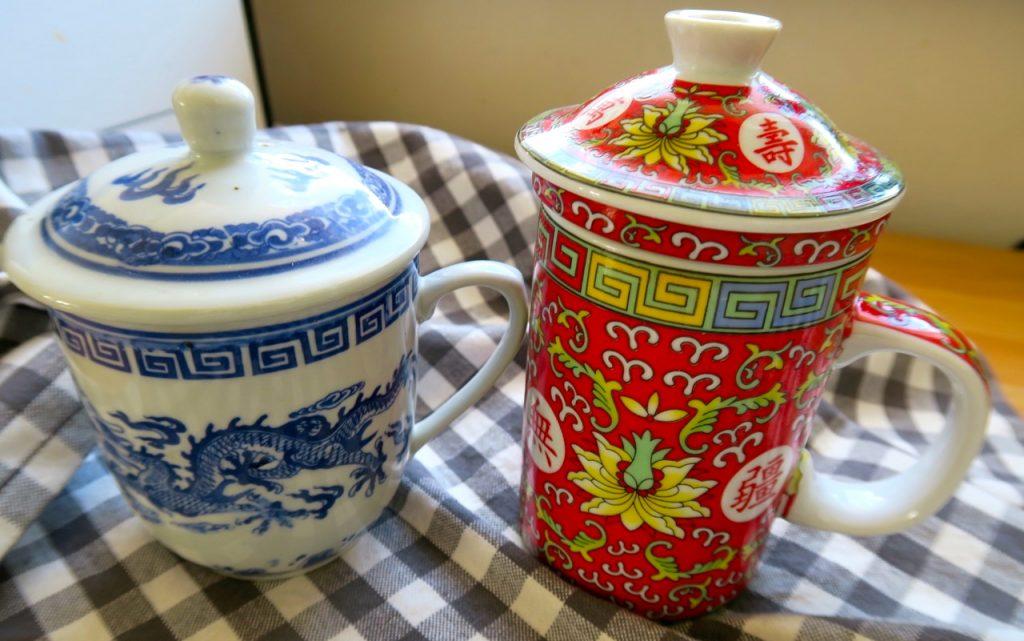 En kinesisk mugg för te är praktisk och har lock för att behålla värmen och en lös tesil-