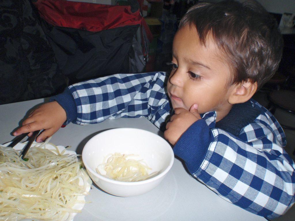 Nudlar i kIna kan ätas på många sätt. Här tränarbarnbarnet Max att äta nudlar med pinnar.