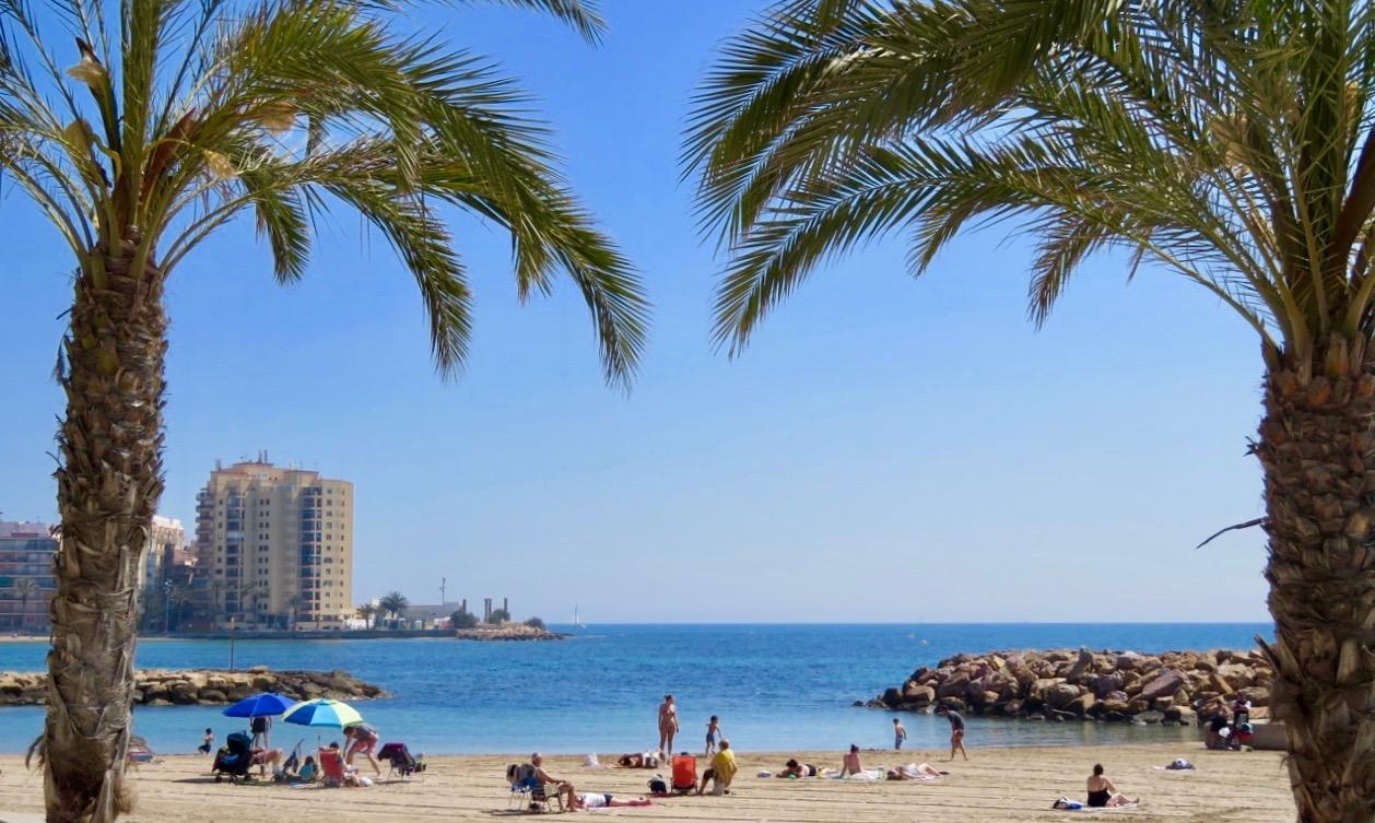 Sommarkänsla med blå himmel och blått ha och folk på stränderna. Här vid Playa de la Cura i Torrevieja.