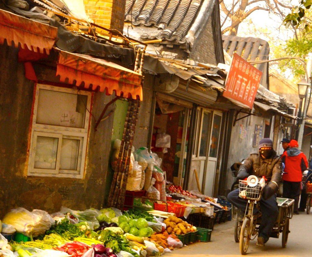 Gatuförsäljning en en hutong i Peking men med en dörr öppen in till dne lilla butiken.