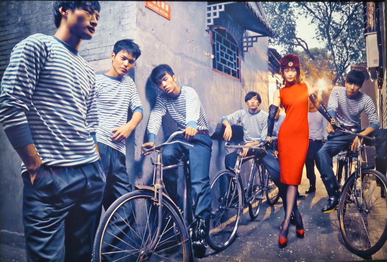 Här modefotografen Chen Mann som bär en röd fodralklänning.