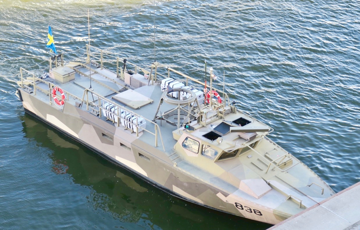 Försvarets Stridsbåt 90 ses sticka ut där den ligger vid kaj och väntar på slussöppningen.