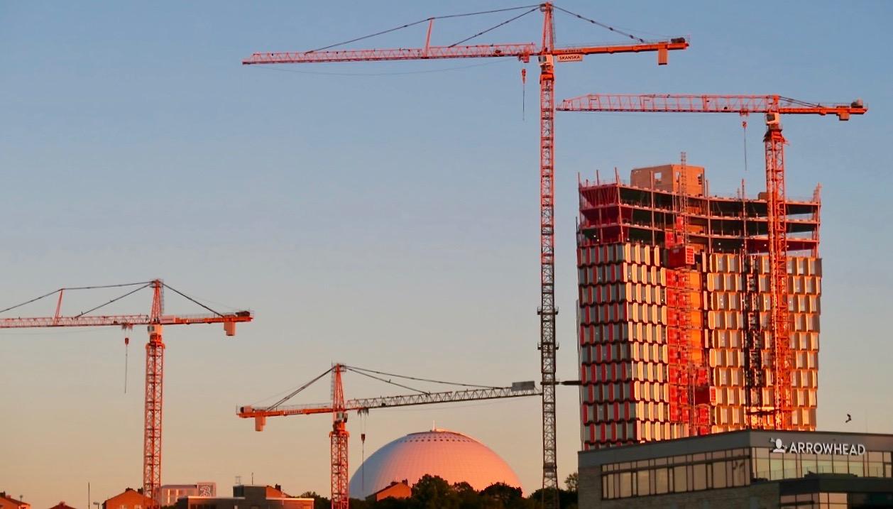 Höga lyftkranar vid byggandet av skyskrapen, Stockhom New, i Stockholm. Undrar vad som bär upp dem och hur de är förankrade i marken