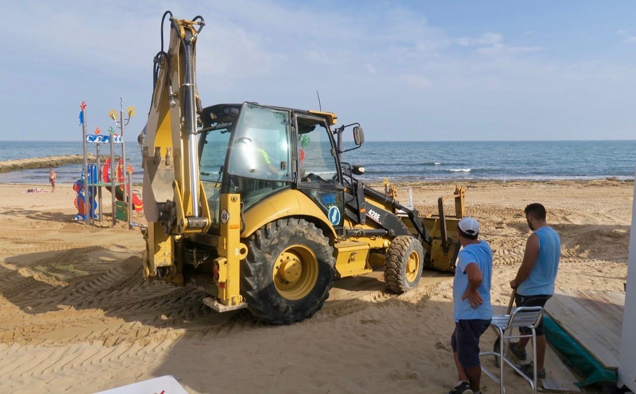Sanden på Los Locos stranden sprids ut. Det är varmt och två står i skuggan och övervakar att det blir rätt.