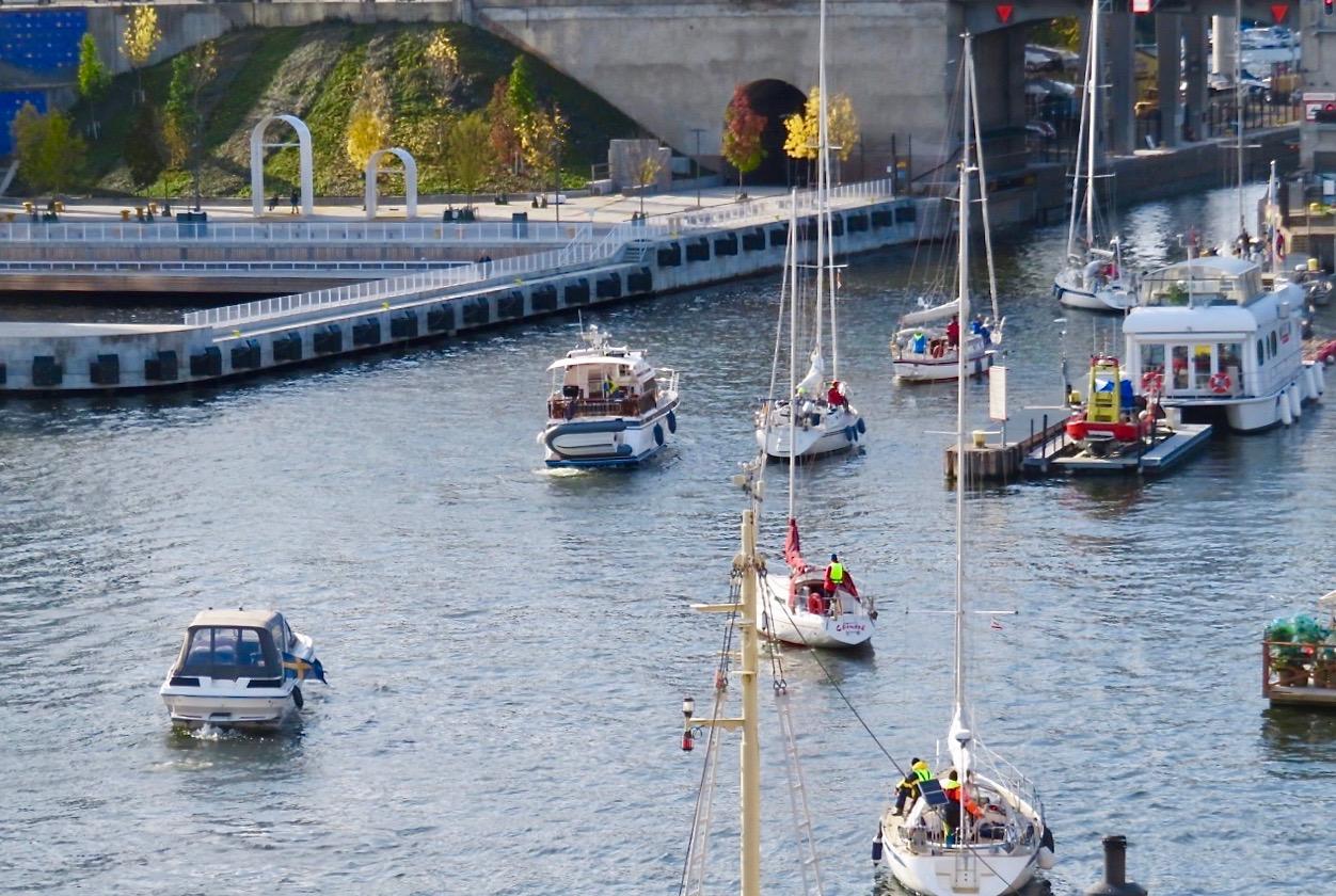 Balkongdörren och ett fönster är öppet och jag blickar ner mot båtarna som ska slussa i Hammarbyslussen.