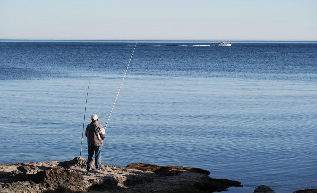 En fiskare prövar sin lycka. Himmel och hav - vackert blått