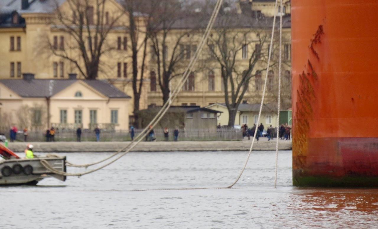 """Många och kraftiga tampar för att ordna med förtöjninge. Men så ligger då ett kinesiskt skepp med en """"guldbro"""" på redden utanför Slussen."""