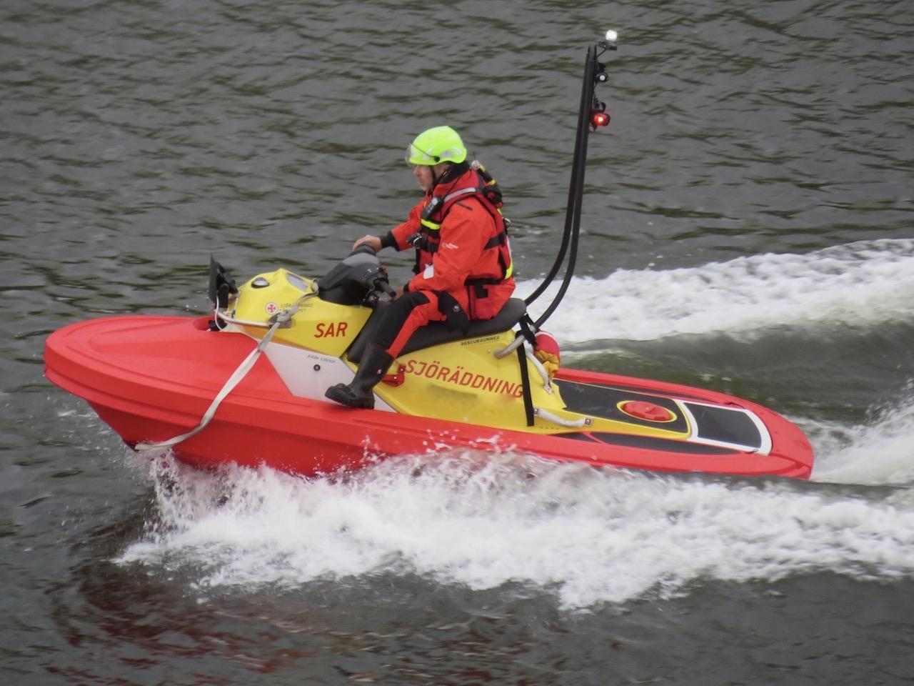Absolut skiftande utsikt. Svanen i Hammarbykanalen får sällskap en en vattenskoter från Sjöräddningen.
