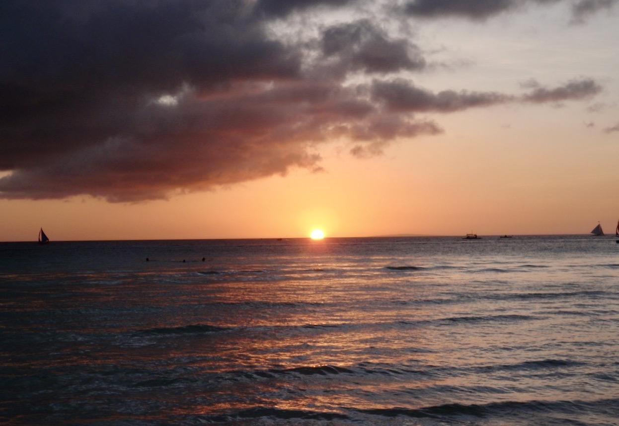 Boracay. Solen har nästan försvunnit i havet och ett dramatiskt moln har dykt upp på himlen.