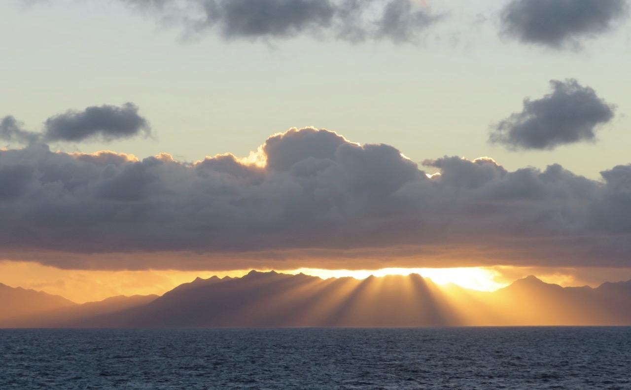 Eldslandet i Sydamerika. Solen stiger upp mellan ett stort moln och de höga bergen