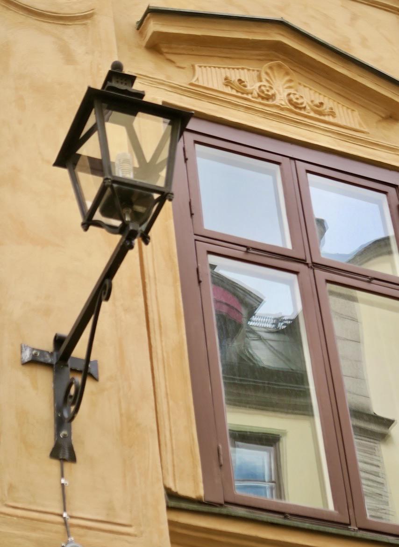 Stockholm. Gamla stan. Kontraster och detaljer. Gatlyktans strama form möter de sirligare utsmyckningarna ovanför fönstret.