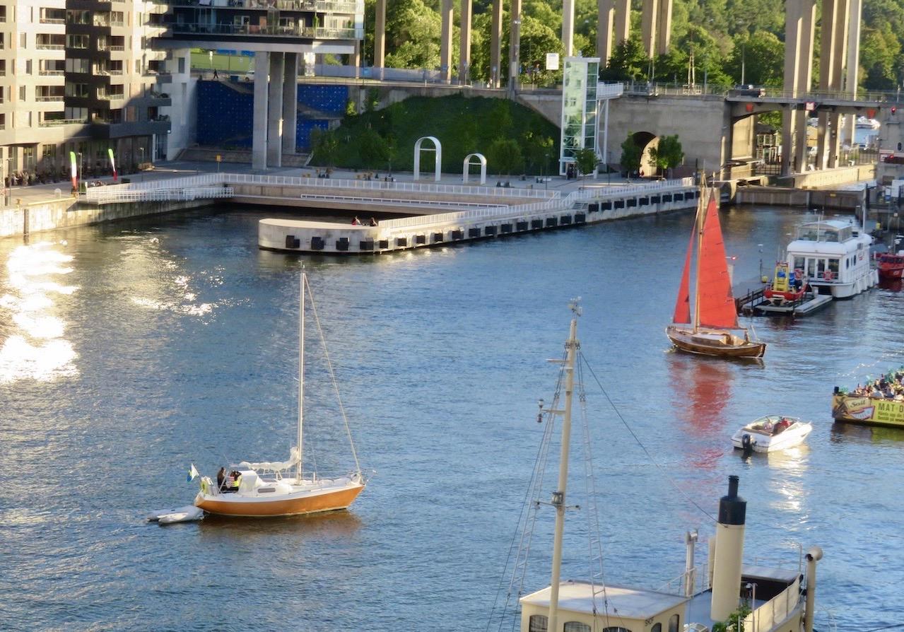 Stockholm. Södermalm. Hammarbyslussen. Båten med de röda seglen har vänt. Och viktigt för att segla är att fånga vinden.