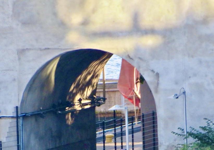Stockholm. Södermalm. Hammarbyslussen. Jag ser de röda seglen skymta genom gång och cykeltunneln. Och visst är det en konst i sig att segla och en särskild utmaning att segla in och genom en sluss. .