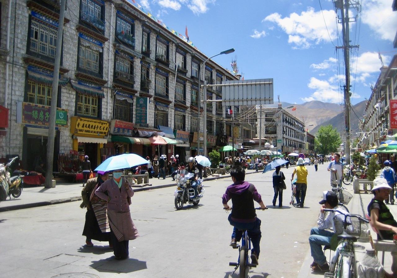 Lhasa. Typisk gatumiljö. Människor är klädda både i traditionella kläder och mer västerländska.