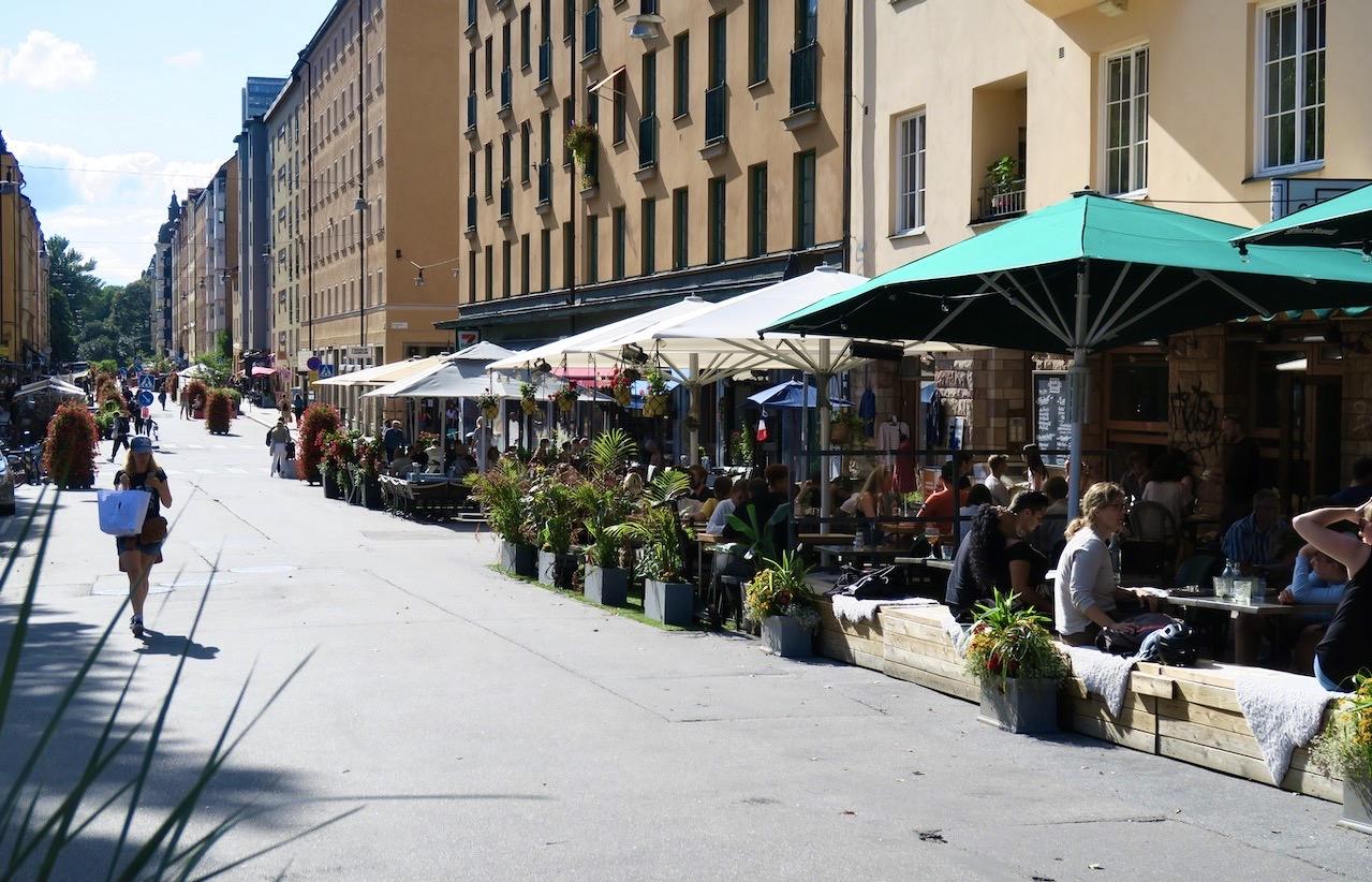 Stockholm. Södermalm. Skånegatan. Jag slår mig ner på en bänk och tar där del av det storstadsvimmel som pågår denna eftermiddagsom