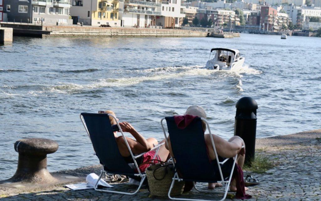 Stockholm. Södermalm. Danvikskanalen. Här satt flera vid vattnet som också hade med sig picknick och stolar.