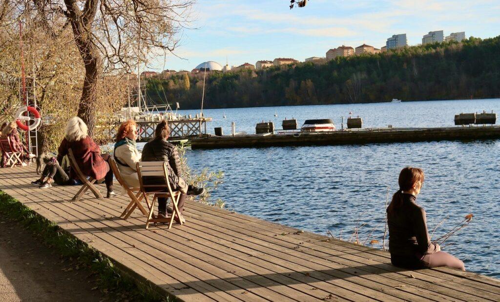 Stockholm. Södermalm. Årstaviken. Flera njuter på bryggan denna strålande höstdag.