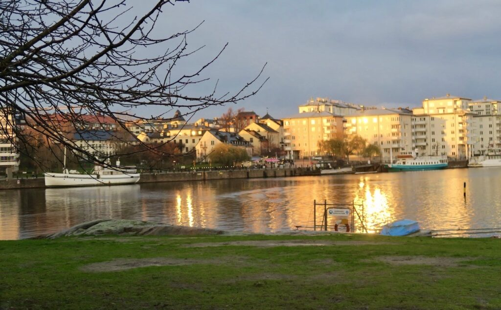 Hammarby sjöstad. Vi håller oss vid vattnet och på gångvägen . Stannar till och ser solen spegla sig i husfönstren på Södersidan.