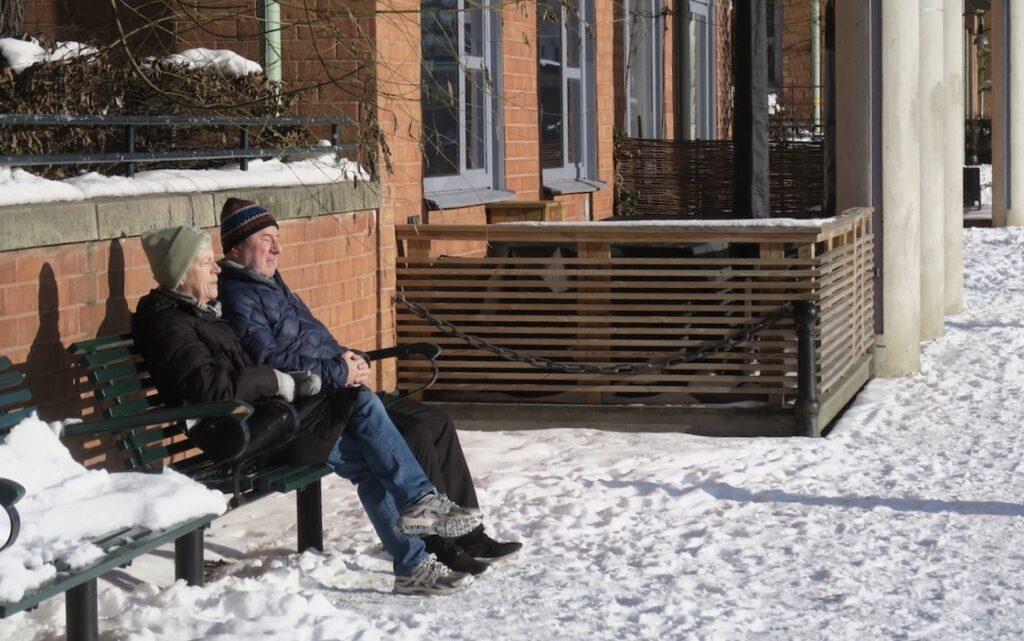 Stockholm. Södermal. Ett par har satt sig på en bänk för att mysa i eftermiddagssolen.
