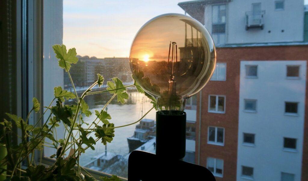 Stockholm. Hemma. Södermalm. Solen ses för en kort stund blixtra till i en lampa för att övergå till att bli en låga under några minuter.