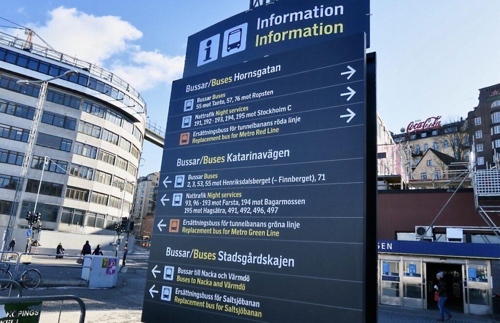 Stockholm. Södermalm. Slussen. En tydlig skylt visar information om åt vilka håll man ska gå för att hitta rätt buss .