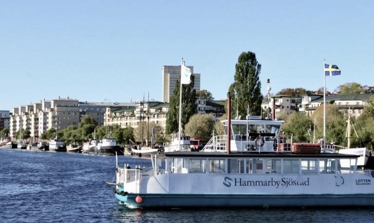 Stockholm. Södermalm. Mycket blått och i olika nyanser. Vlå himmel, svensk flagga icg den blå färjan över till Hammarby sjöstad.