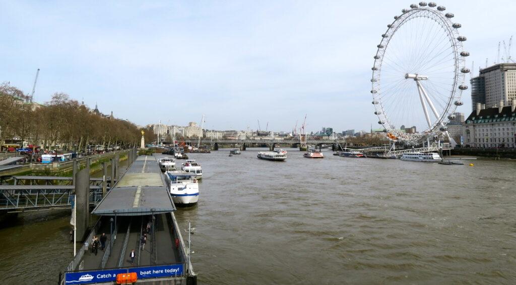 London Themsen och London Eye. Båtarna ser inte ut att gunga men gungar gör pariserhjulet Londomn Eye.