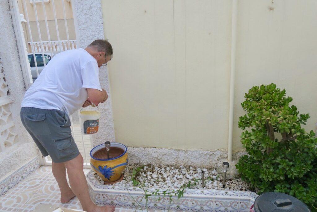 Torrevieja. Spanien.Maken passar på att öfrbättra färgen på murväggen när passionsblomman ligger utsträckt på terrassen.