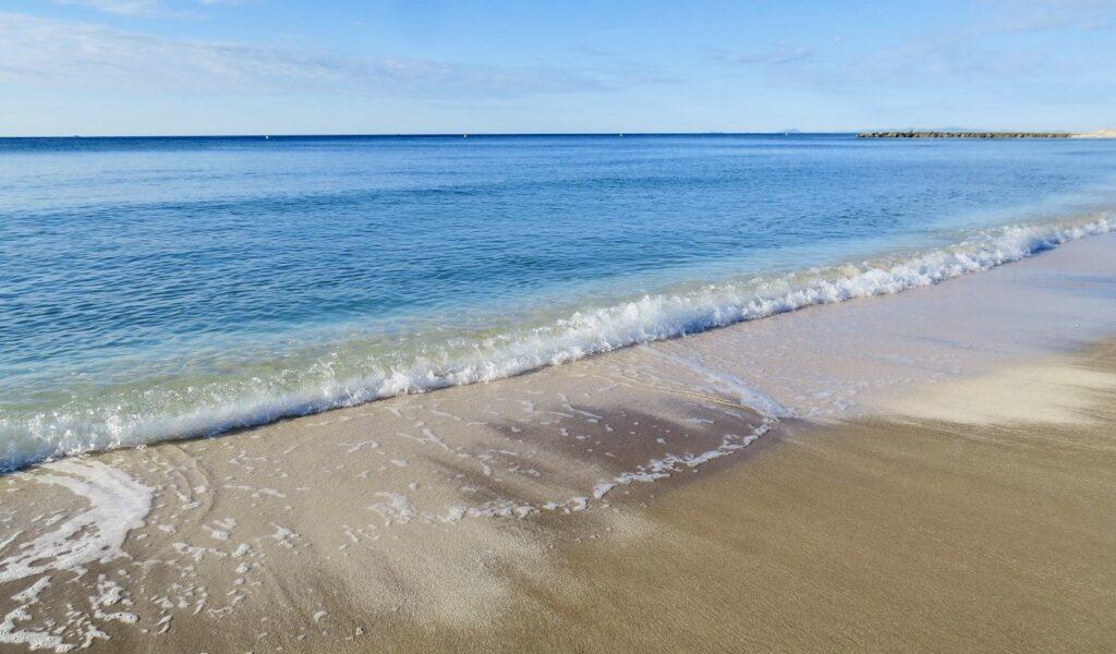 Torrevieja. Stranden Los Locos. Även vågorna rullar in mjukt denna stilla morgon