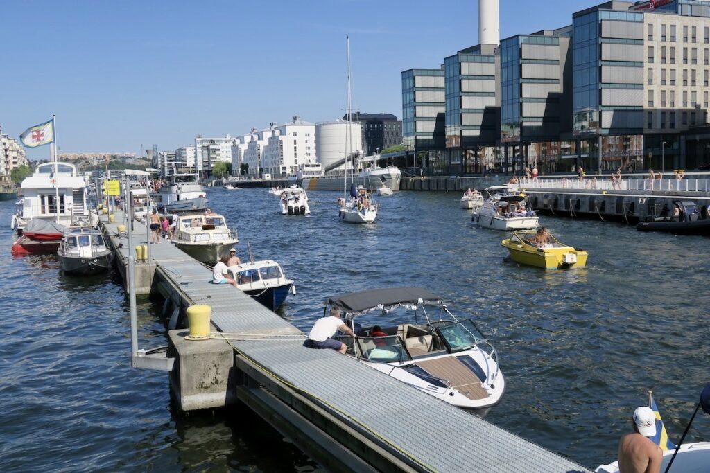 """Stockholm. Södermalm. Hammarbyslussen . En del båtar väntar vid Sjöräddningens brygga och andra har fått """"parkera"""" i kanalen."""