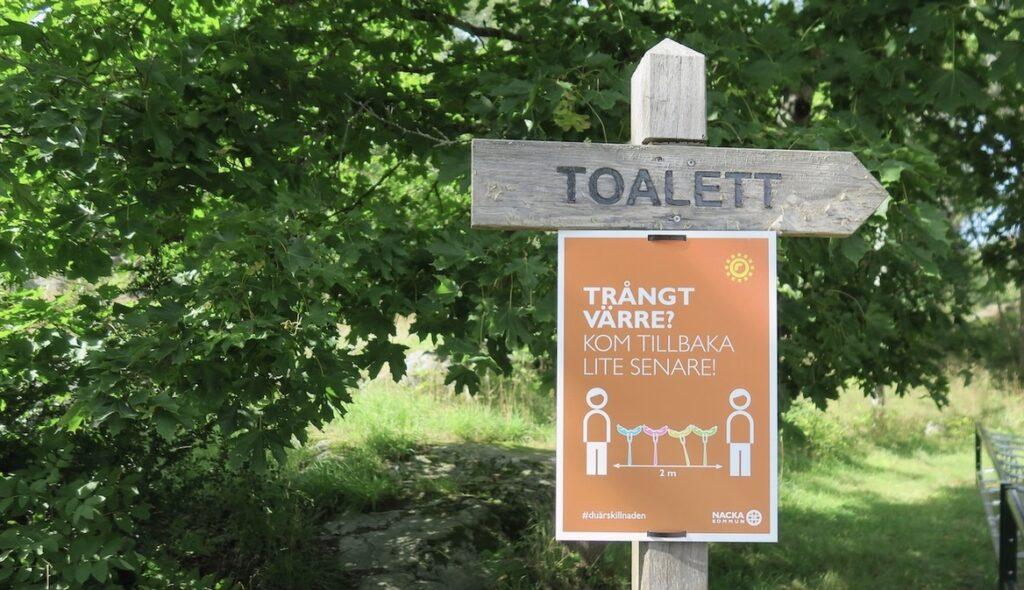 Nacka. Nyckelvikens herrgård. En diskret toalettskylt inbäddad i grönska.