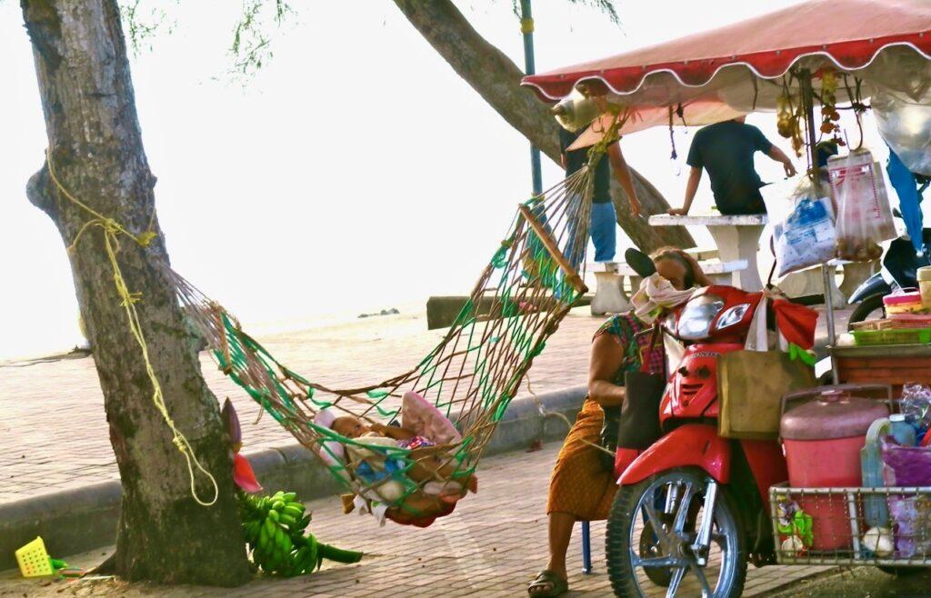 Thailand. Mae Phim. Denna kvinna med sin ambulerande butik ville gärna sälja ananas och juice till oss.