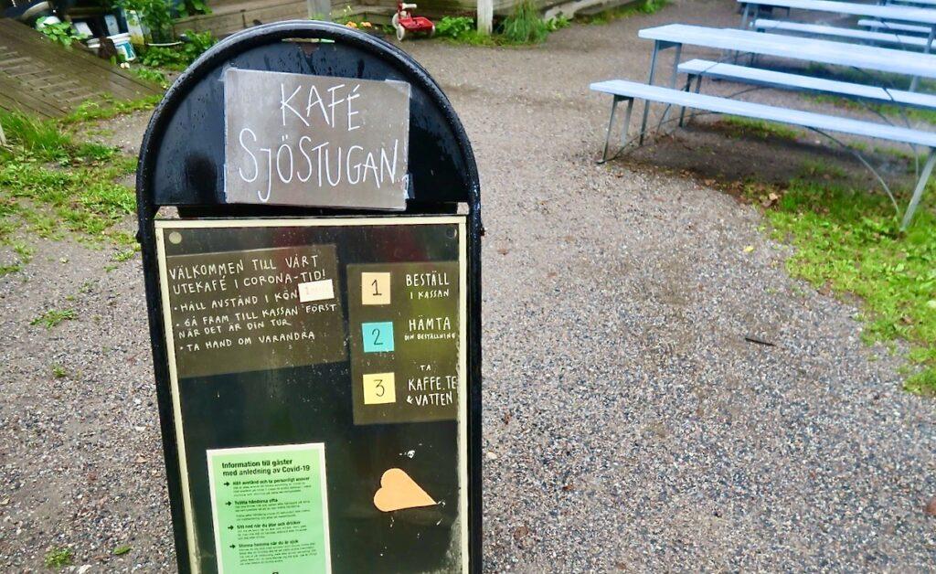 Bergshamra by i Solna. Upplysande skyltar vid Kafé Sjöstugan som visar vad som gäller och hur man beställer.
